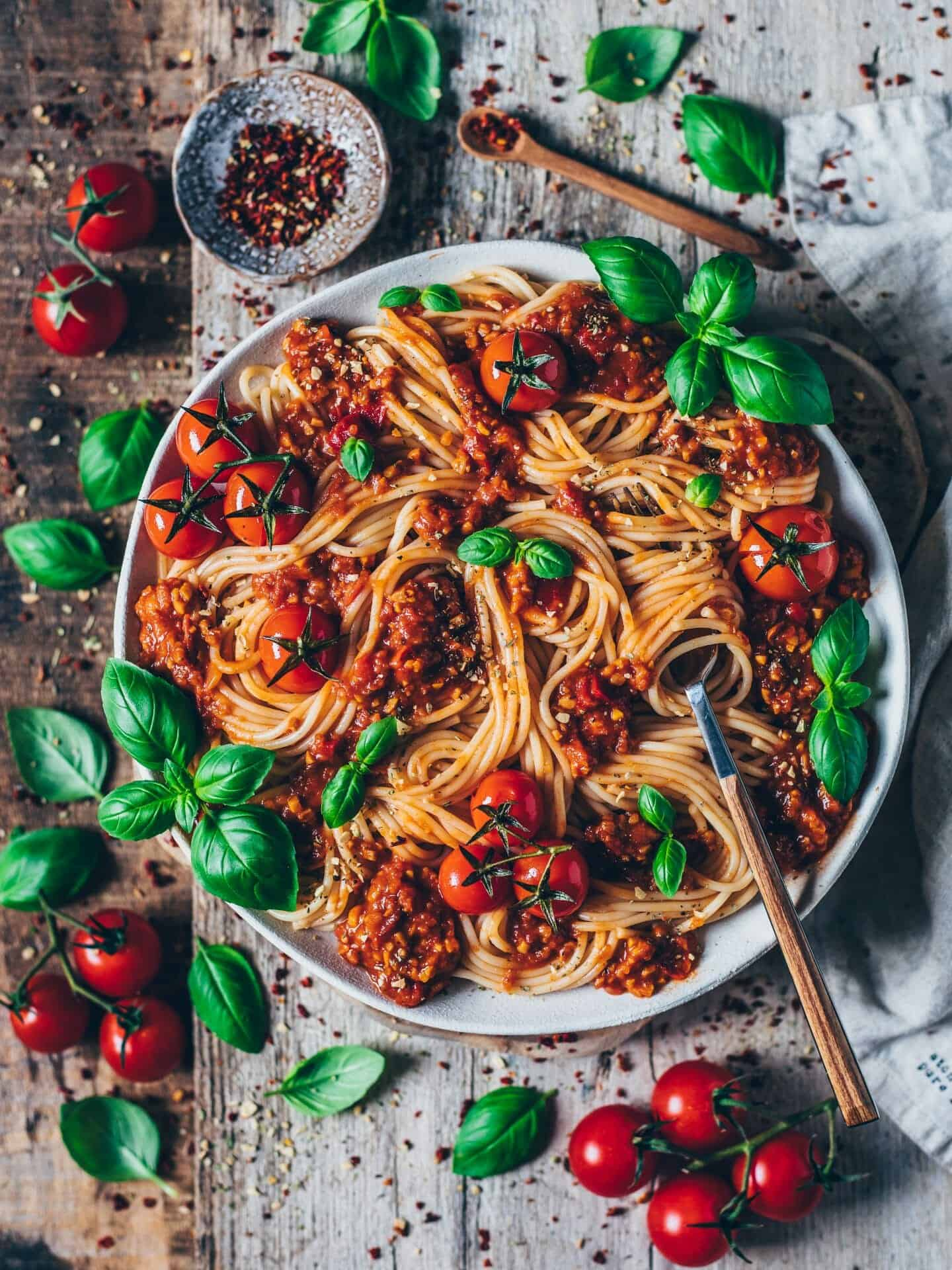 spaghetti noodles with bolognese sauce tomatoes and basil