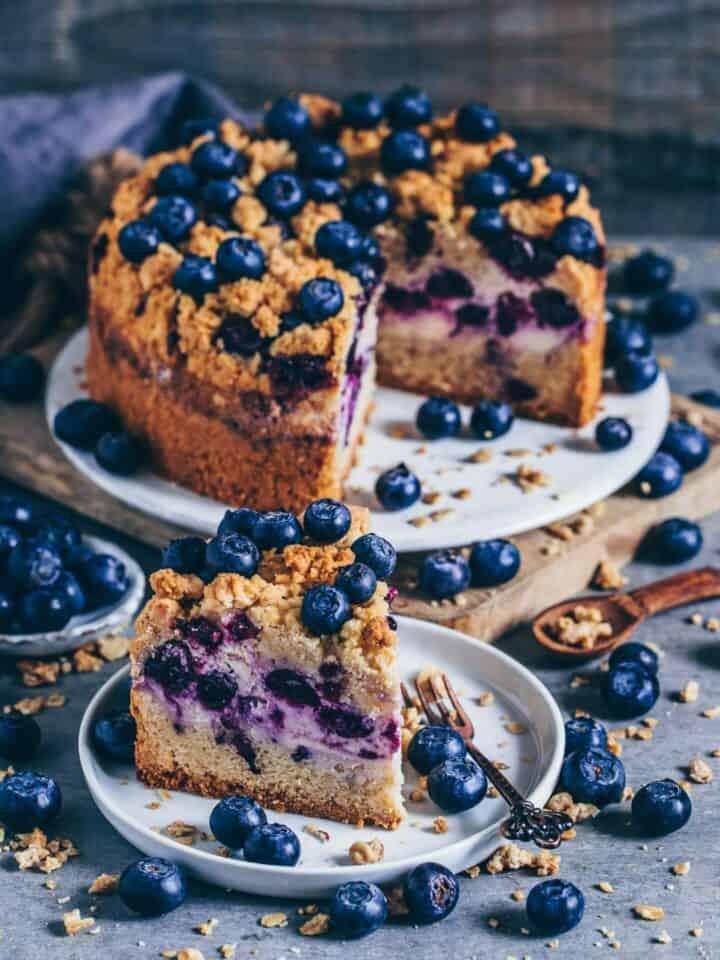 Ein köstlicher veganer Streuselkuchen trifft auf cremigen Käsekuchen - Dieser leckere vegane Streuselkuchen ist kein gewöhnlicher Streuselkuchen, denn er enthält noch eine cremige Käsekuchenschicht mit saftigen gesunden Blaubeeren, die ihn noch leckerer macht. Dieser Kuchen schmeckt nicht nur so unglaublich gut, sondern er ist auch einfach zu machen. Man kann den Kuchen übrigens auch glutenfrei zubereiten und das Obst nach Belieben variieren.