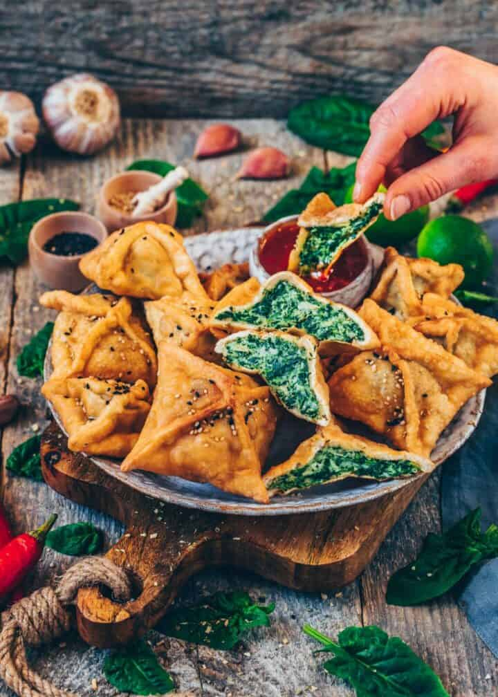 These crispy Spinach Artichoke Wontons make for the perfect snack, appetizer, or lunch! They're made with Homemade Wonton Wrappers and filled with a creamy & cheesy Spinach Artichoke Dip! This easy Recipe includes step-by-step pictures showing you how to wrap them.