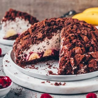 This German vegan Mole Cake is a delicious Banana Cream Chocolate Cake which is quick and easy to make. It's made of a soft Chocolate Crumble Cake and filled with bananas, whipped stracciatella cream, and cherry compote. This recipe includes step-by-step pictures.