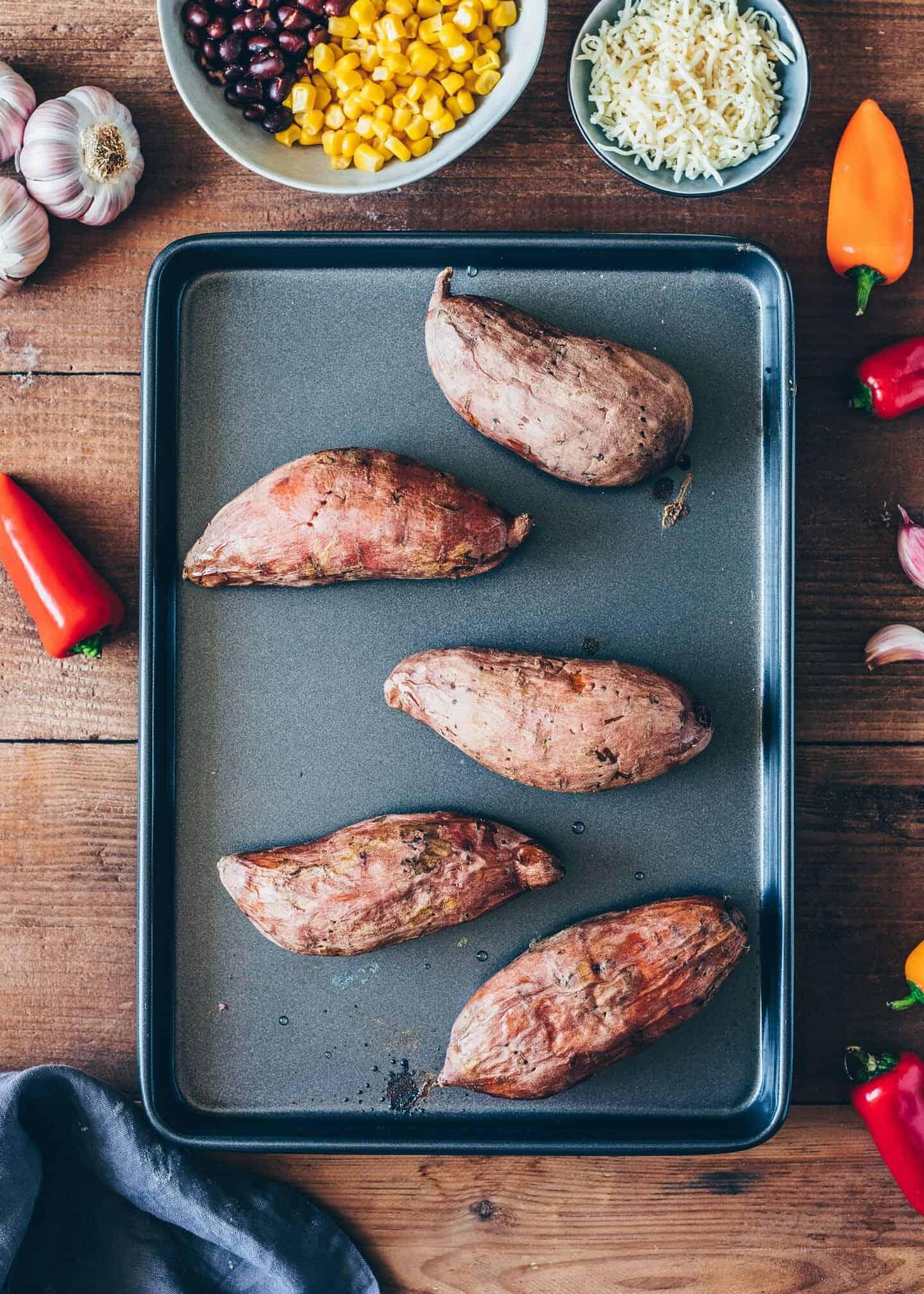 Mexikanisch gefüllte Süßkartoffeln mit schwarzen Bohnen, Mais, Paprika und veganem Käse ist einfach zubereitet, gesund und lecker. Dazu Avocado-Aioli als perfekte Haupt-Mahlzeit oder Beilage. Einfaches Rezept. Vegane Ofen-Kartoffeln.