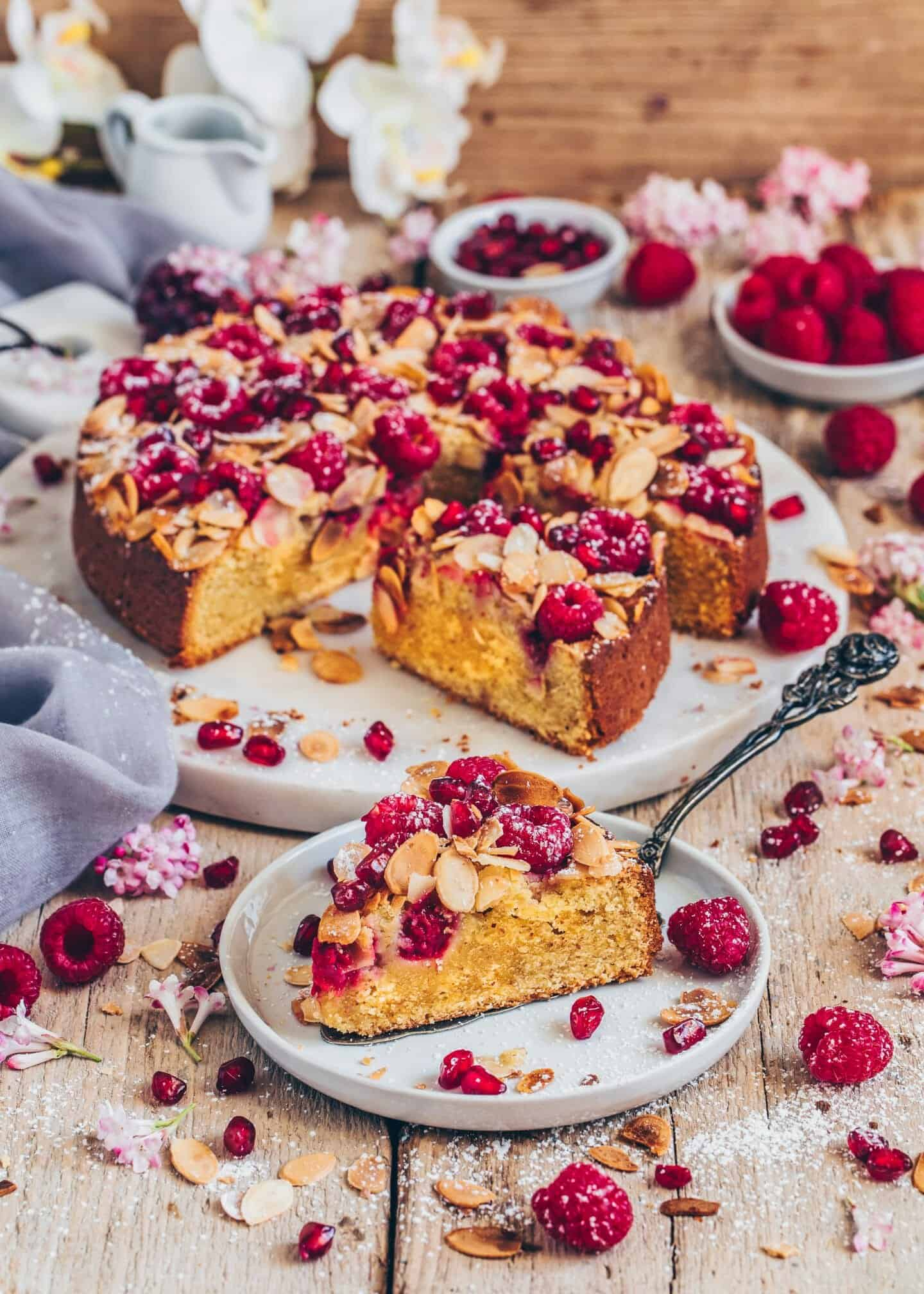 Rezept für Mandel-Orangen-Kuchen mit Himbeeren. Er ist einfach und schnell zubereitet, vegan, saftig, weich, fluffig, gesund, glutenfrei, ohne Eier, ohne Milch. Den Rührkuchen (Mandel-Kuchen) kann man mit jedem Obst belegen.