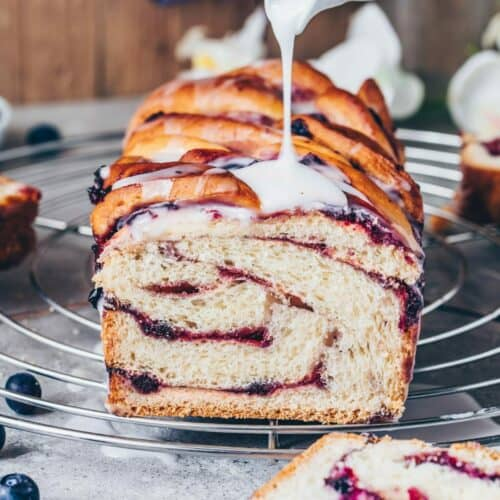 Vegan Blueberry Babka is a soft and fluffy brioche like Twist Bread with fruity swirls of jam and lemon glaze. This Recipe is easy, delicious, egg-free, healthy, and includes step-by-step pictures!