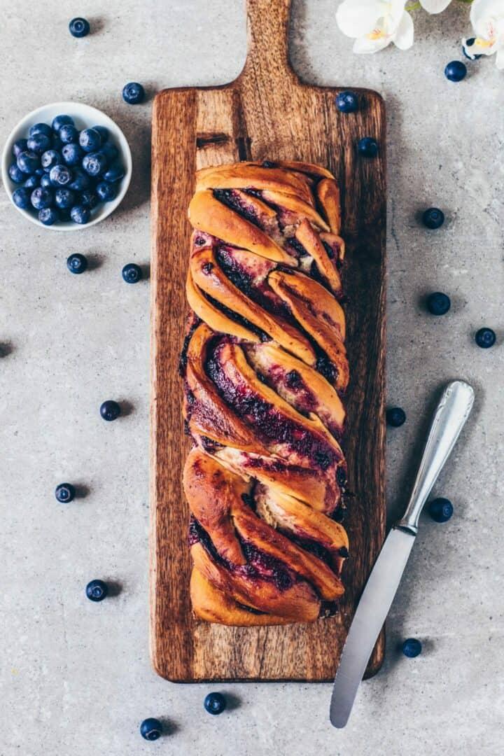 Blaubeer Babka ist ein veganer Hefezopf, der mit fruchtiger Marmelade gefüllt ist. Das fluffige Brot ist mit einer Zitronen-Glasur überzogen, sodass es perfekt als süßes Frühstück, Dessert, Brunch oder Snack ist. Besonders zu Ostern als Oster-Brot! DasRezept ist einfach und enthält eine Schritt-Anleitung mit Bildern.