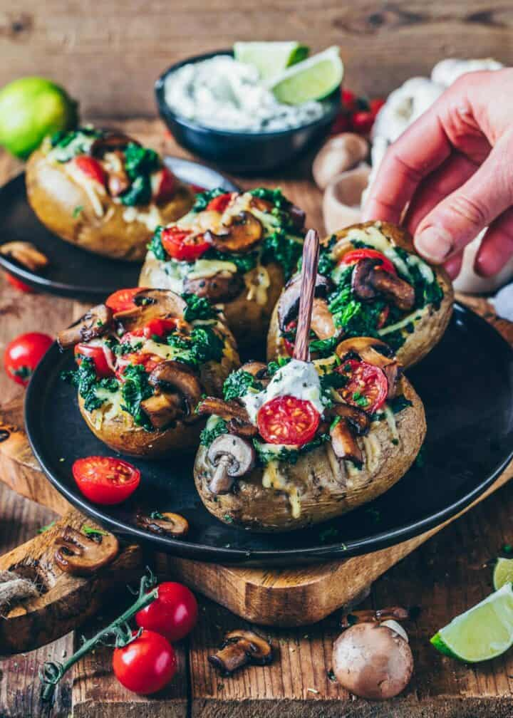 Easy stuffed baked potatoes with spinach, mushrooms, tomatoes, and vegan cheese. This oven baked potato recipe with herb dip is simple, healthy, delicious with veggie filling!