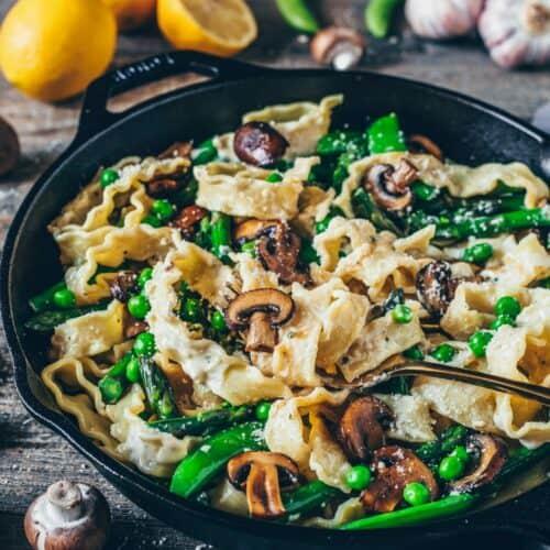 Creamy Pasta Primavera with asparagus, mushrooms, peas and vegan parmesan is healthy, delicious, easy pasta recipe. Gluten-free, dairy-free, plantbased.