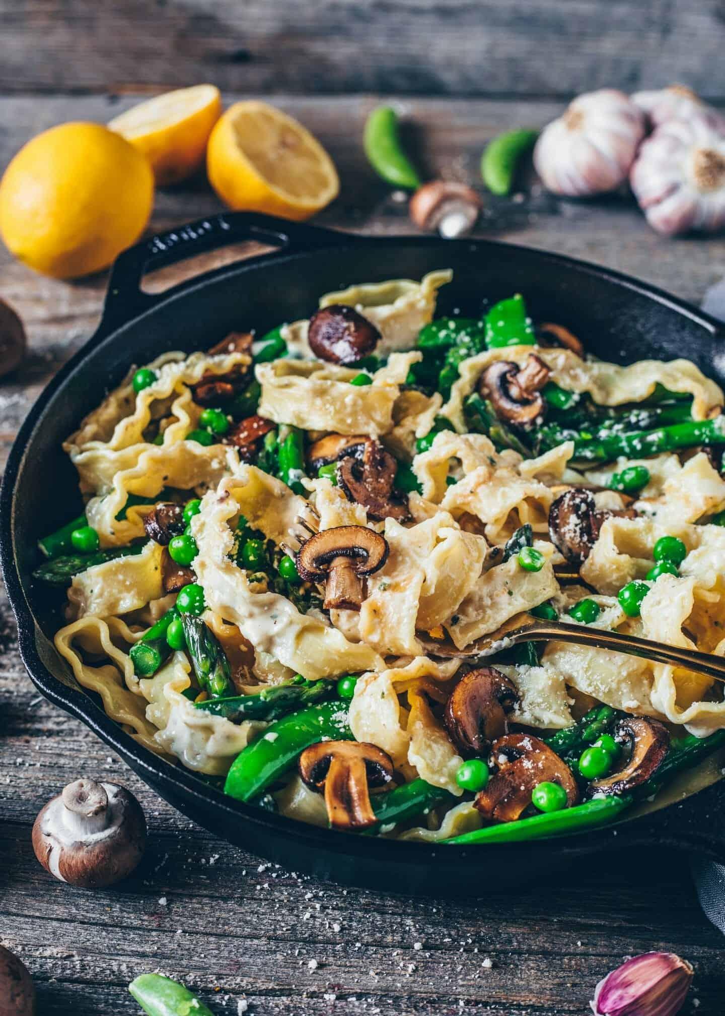 Cremige Pasta Primavera. Nudeln mit grünem Spargel, Pilzen, Erbsen und veganer Parmesan. Gesund, lecker, einfach und schnell. Pasta-Rezept. Glutenfrei, gesund, michfrei.