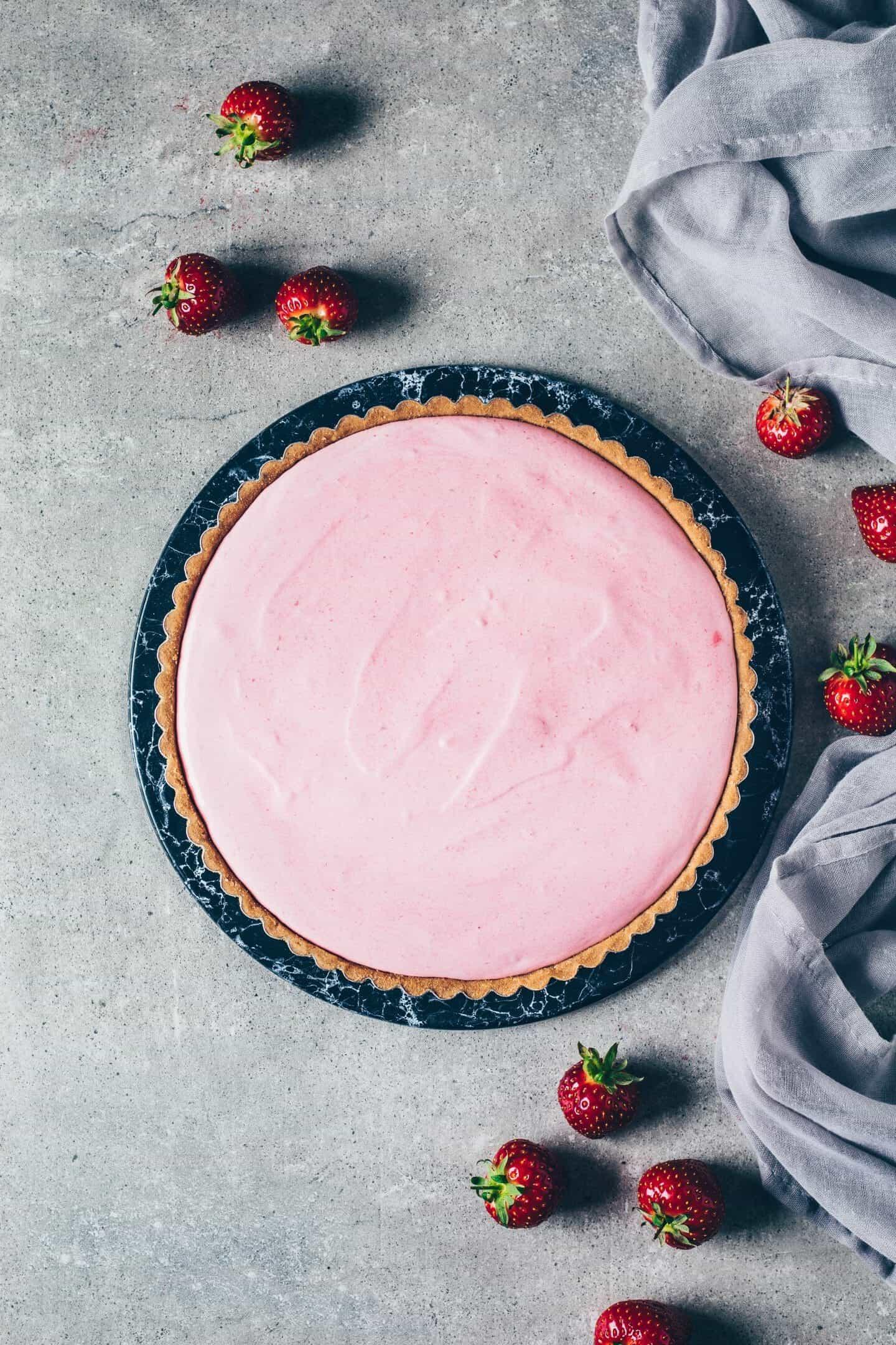 Einfache Erdbeer-Eistorte Rezept. Selbstgemachtes Erdbeer-Eis auf knusprigem Keksteig. Vegan, milchfrei, erfrischendes Sommer-Dessert.