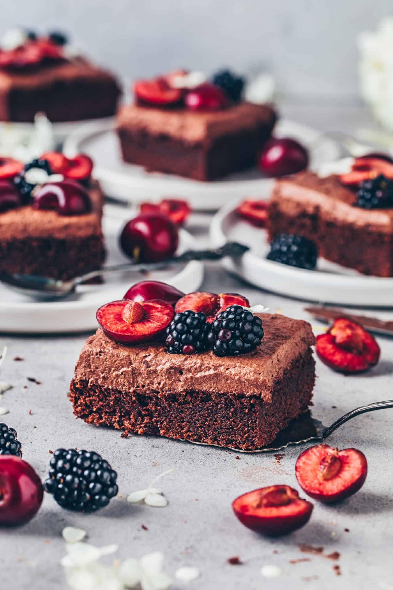 Schokokuchen. Veganer Schokoladenkuchen mit Schoko-Frosting, Kirschen und Brombeeren.