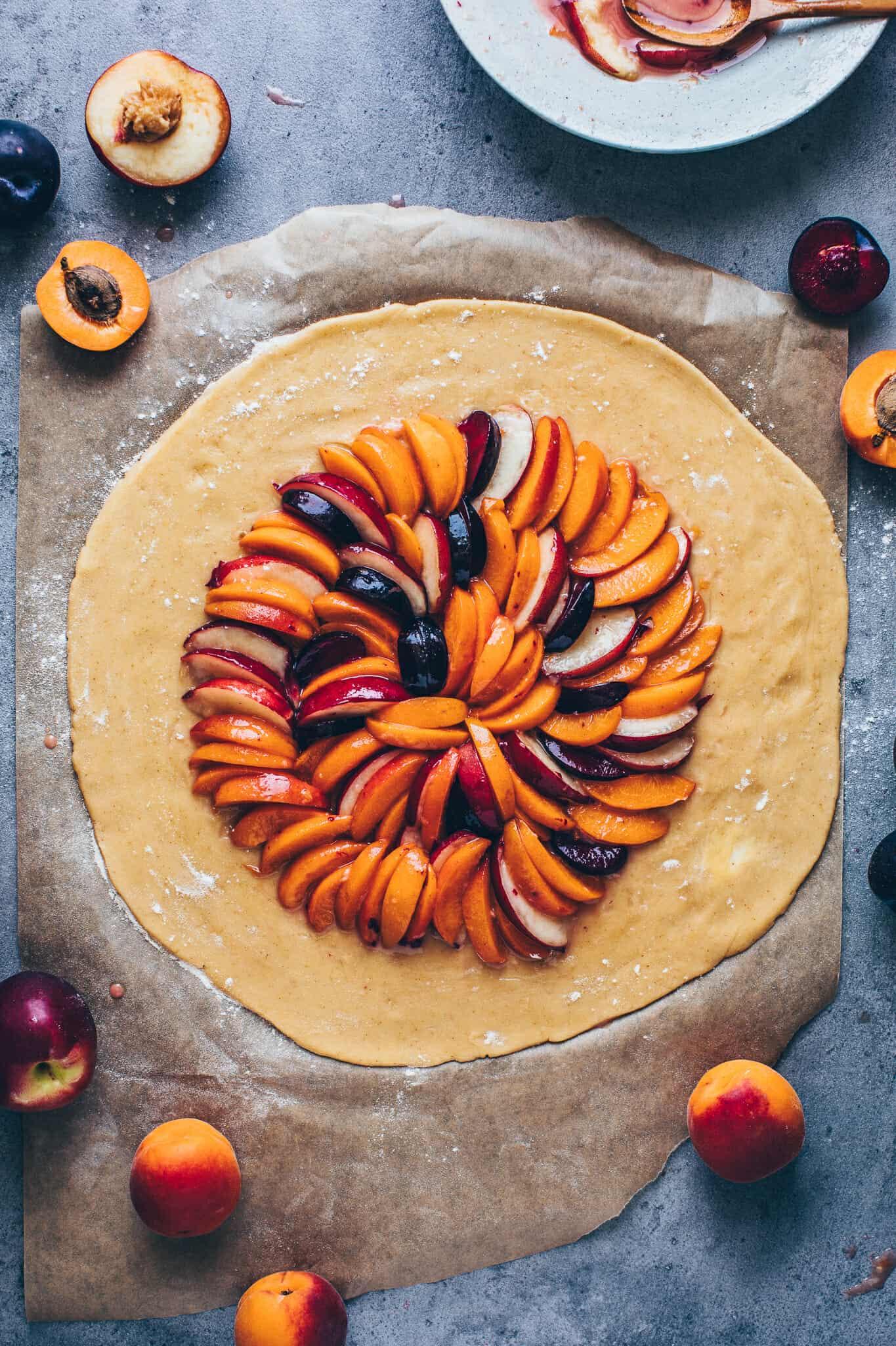 Obst Tarte. Galette mit Mandeln, Pfirsichen, Aprikosen, Nektarinen, Pflaumen. Selbstgemachter veganer Mürbeteig ohne Ei. Glutenfrei, einfach.