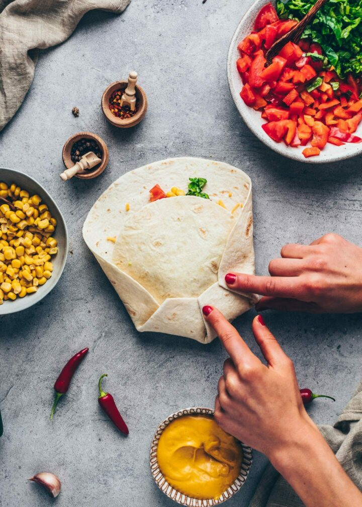 how to make crunchwrap burritos (tortilla with vegan taco meat, cashew cheese sauce, nachos, tomatoes, red bell pepper, corn, shredded cheese, lettuce and mashed avocado)