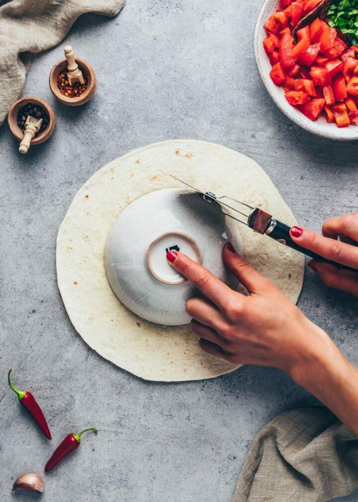 Cut a tortilla into tostada for vegan Crunchwrap supreme
