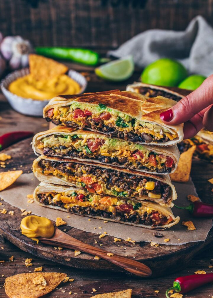 Vegan Crunchwrap Supreme with burrito taco meat filling, cashew cheese sauce, tomatoes, red bell pepper, corn, beans, avocado
