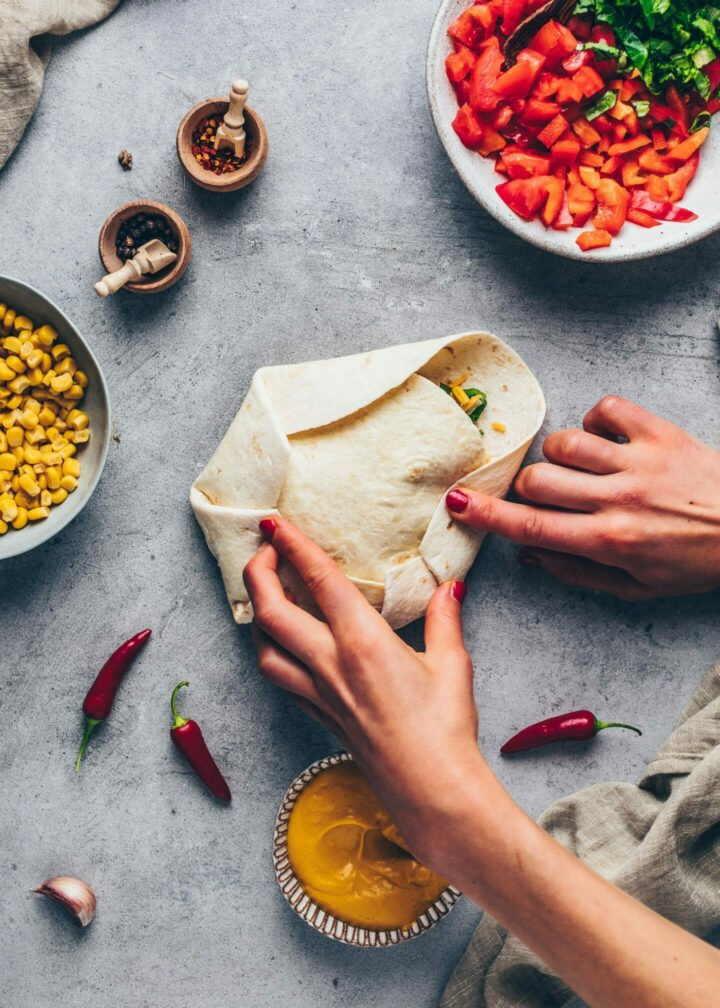 tortilla with vegan taco meat, cashew cheese sauce, nachos, tomatoes, red bell pepper, corn, shredded cheese, lettuce and mashed avocado folded into a Crunchwrap burrito wrap