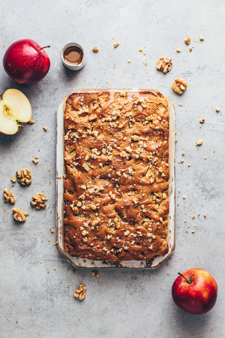 apple bars vegan blondies with caramel sauce and chopped walnuts on a chopping board