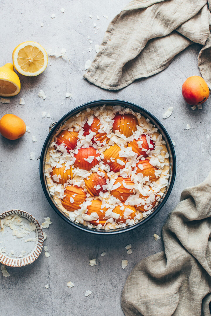 springform pan with cake batter, apricots and coconut flakes