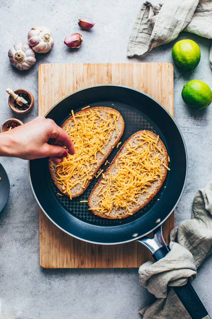 sandwich bread with shredded cheese in a skillet
