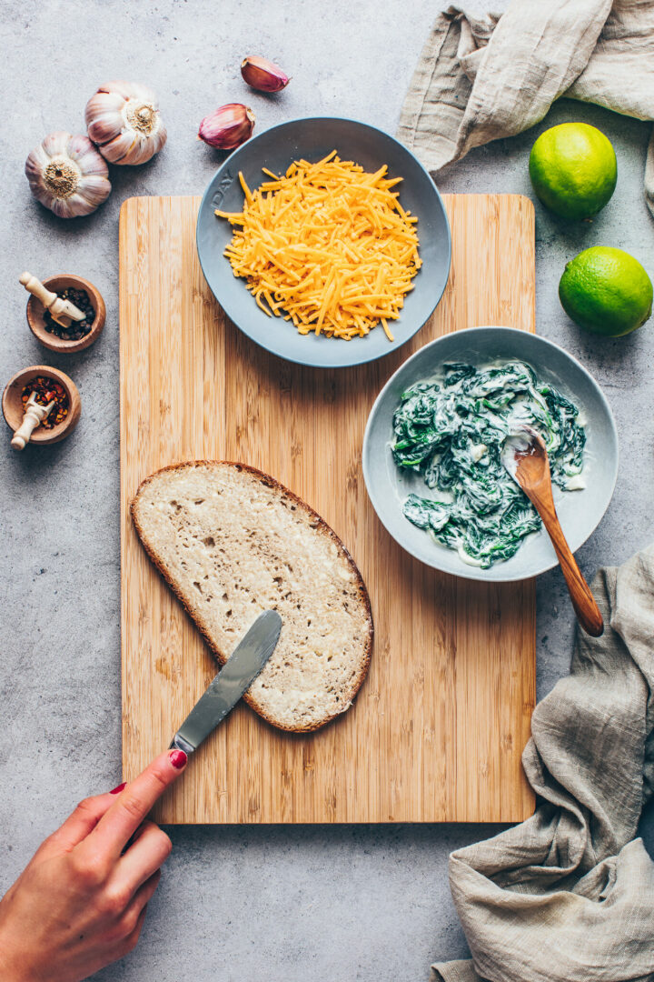 sandwich bread with butter, spinach cream cheese and vegan shredded cheese