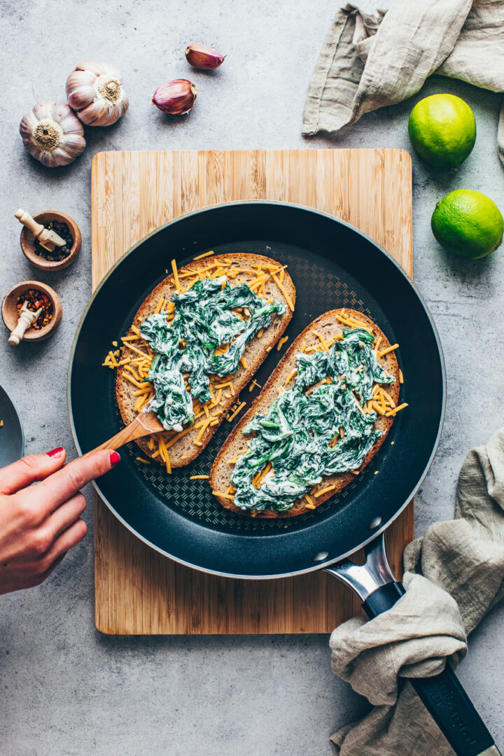 sandwich bread with spinach cream and shredded cheese in a skillet