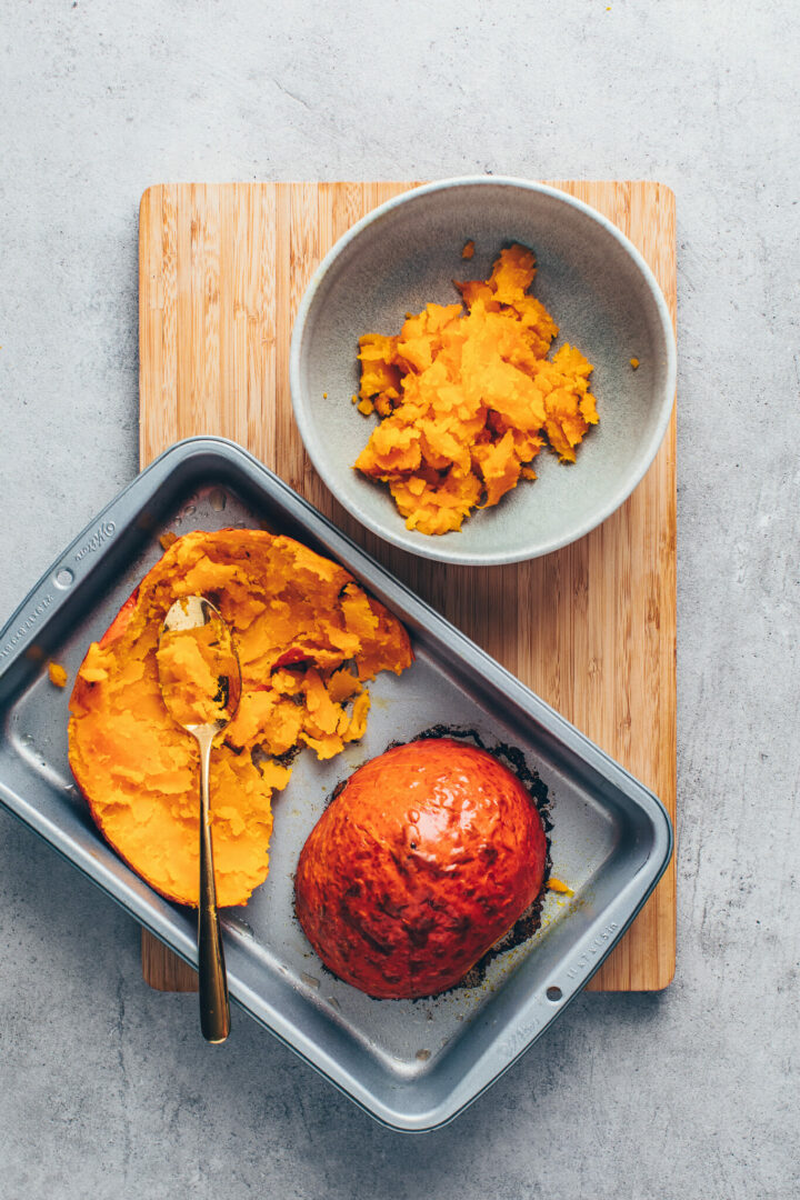 scoop out roasted pumpkin to make pumpkin puree from scratch