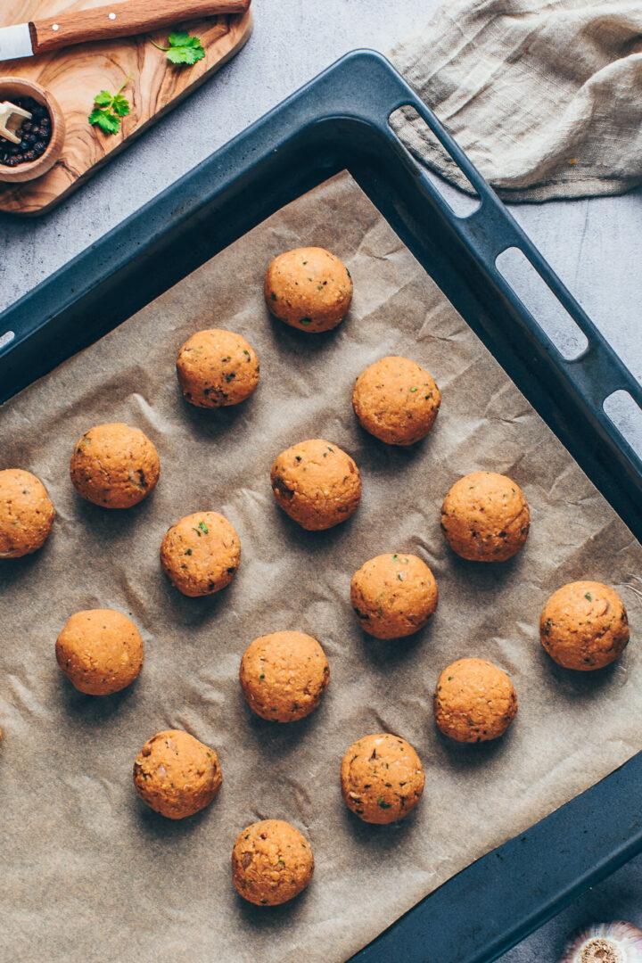 lentil balls on a baking sheet lined with parchment paper (falafel, vegan and vegetarian meatballs)