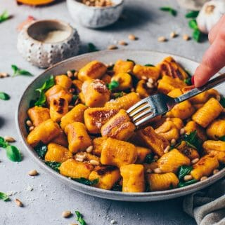 Crispy Pumpkin Potato Gnocchi with spinach, sage, pine nuts and vegan parmesan in a bowl (vegan dumplings)