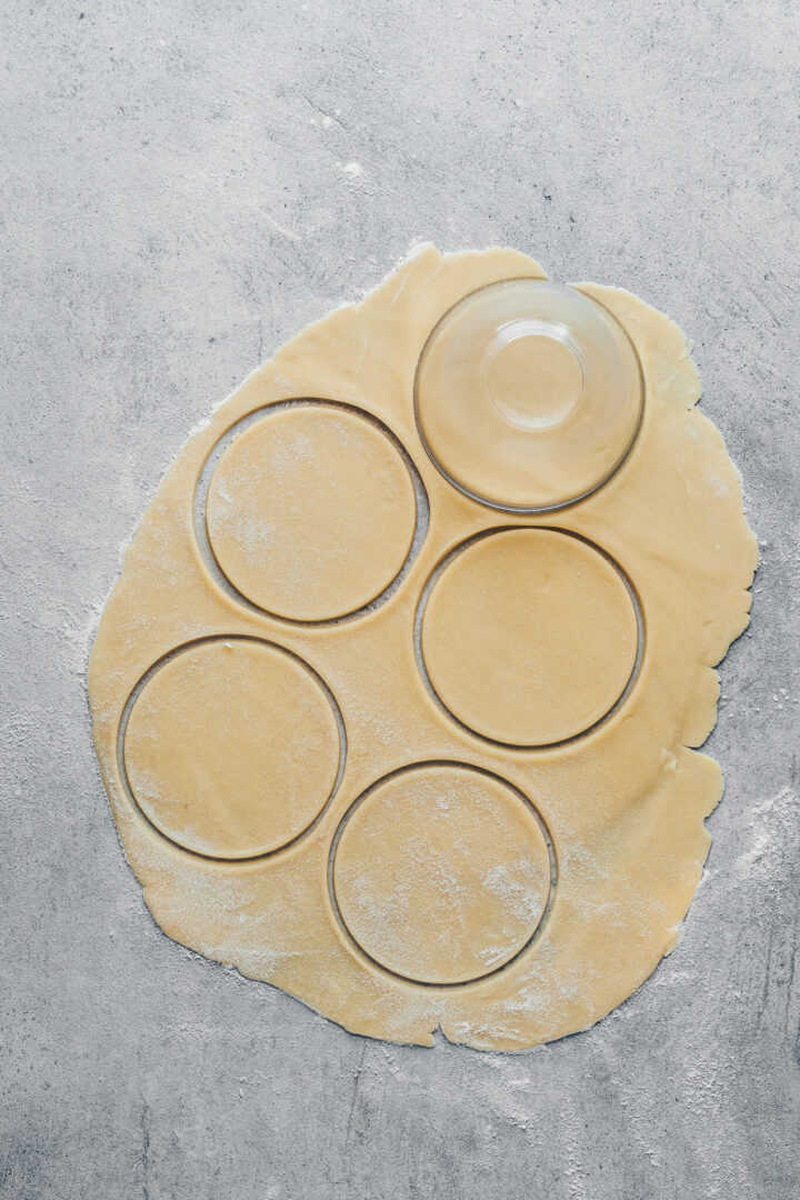 cut out circles of pie crust dough for mini apple pies