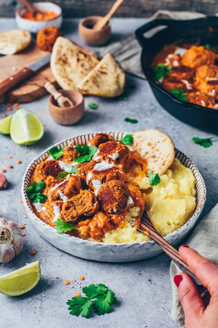 Linsenbaellchen in Indischer Curry Tikka Masala Sauce mit Kartoffelpueree, Kokosmilch, Sesam, Koriander, Petersilie, Knoblauch in einer Schuessel (Cremige Tomaten-Paprika-Sauce mit veganen Meatballs)
