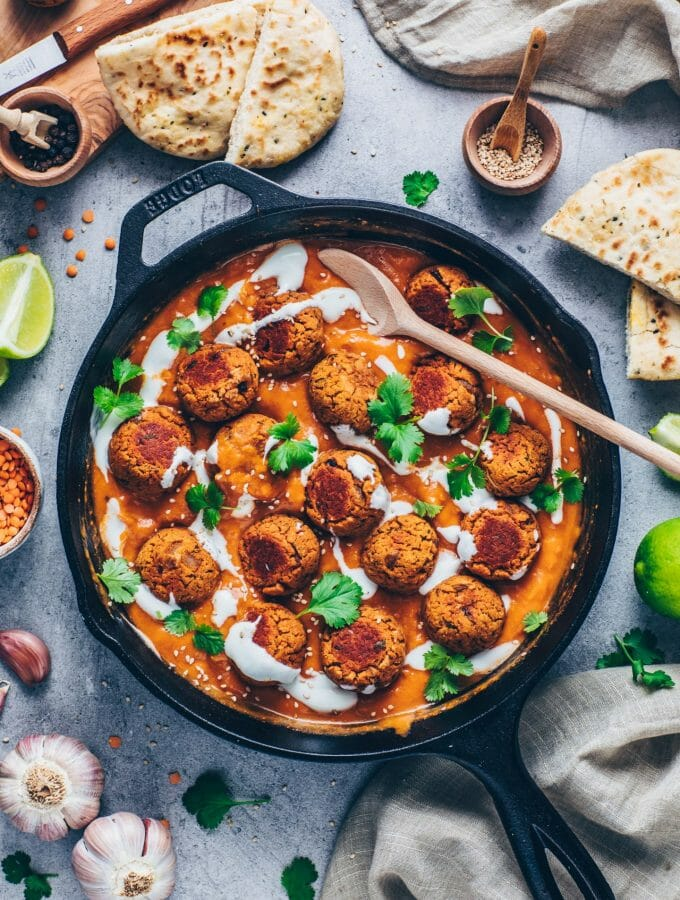 Lentil balls in Indian Curry Tikka Masala Sauce with chopped coriander, sesame, coconut yogurt, garlic, lime, and naan bread (vegan and vegetarian meatballs with creamy tomato roasted pepper sauce)