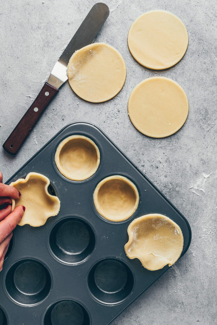 place circles of dough in a muffin pan for mini pies