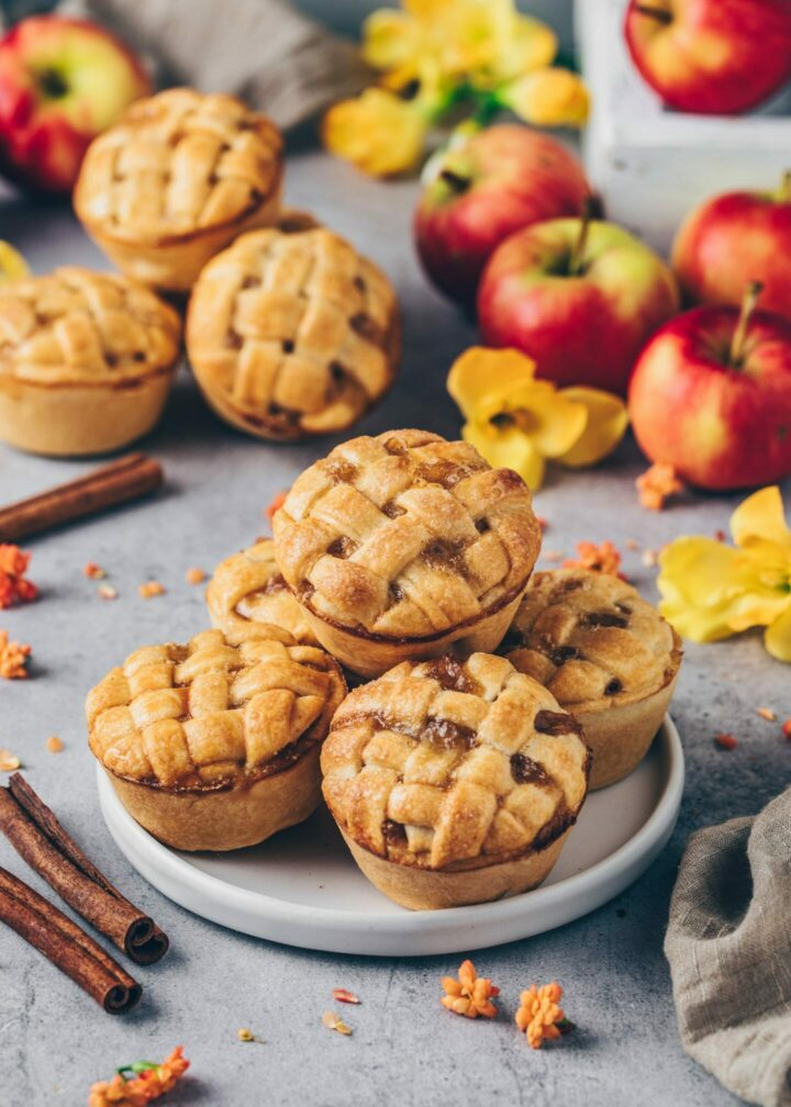 Mini Apple Pies on a plate with apples, cinnamon and flowers