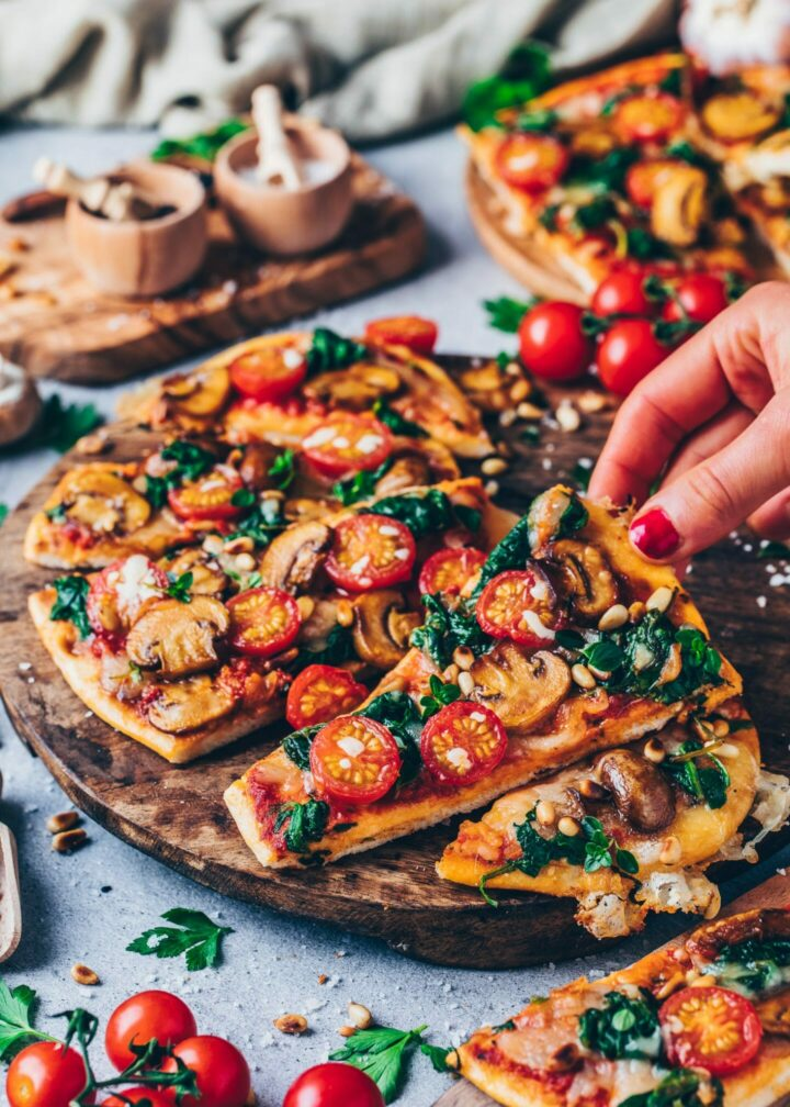 Vegan naan pizza with mushrooms, tomatoes, cheese and spinach