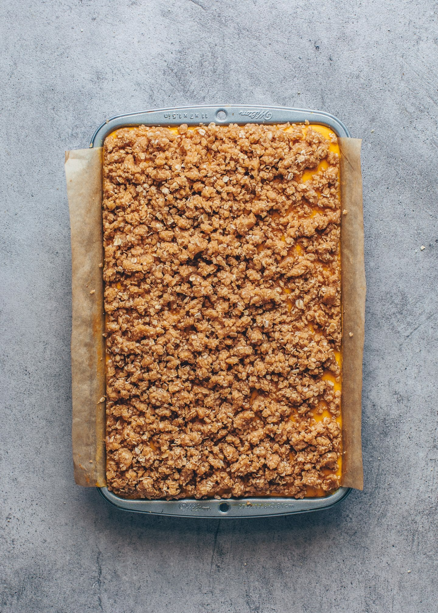 pumpkin cheesecake with cinnamon streusel topping in a baking pan