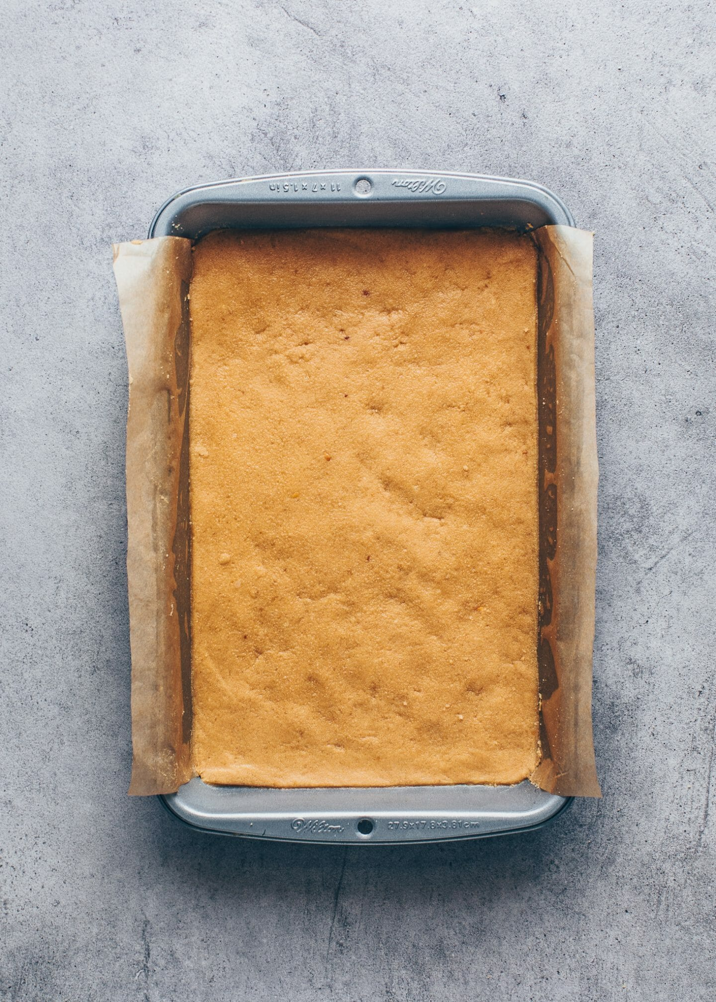 cookie crumb crust pressed into a baking pan lined with parchment paper