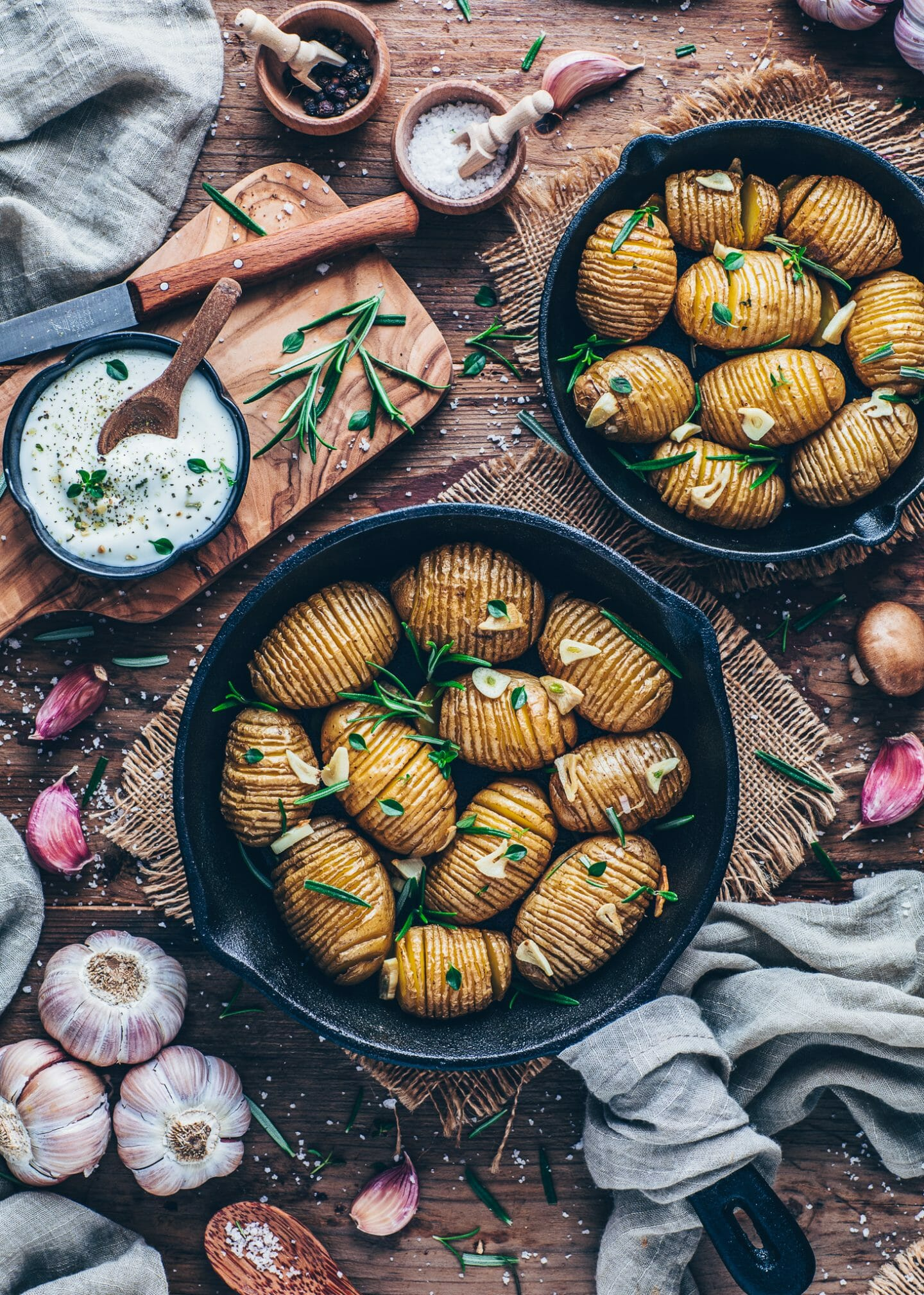 Baked Hasselback Potatoes with garlic, sea salt, rosemary, thyme in a skillet