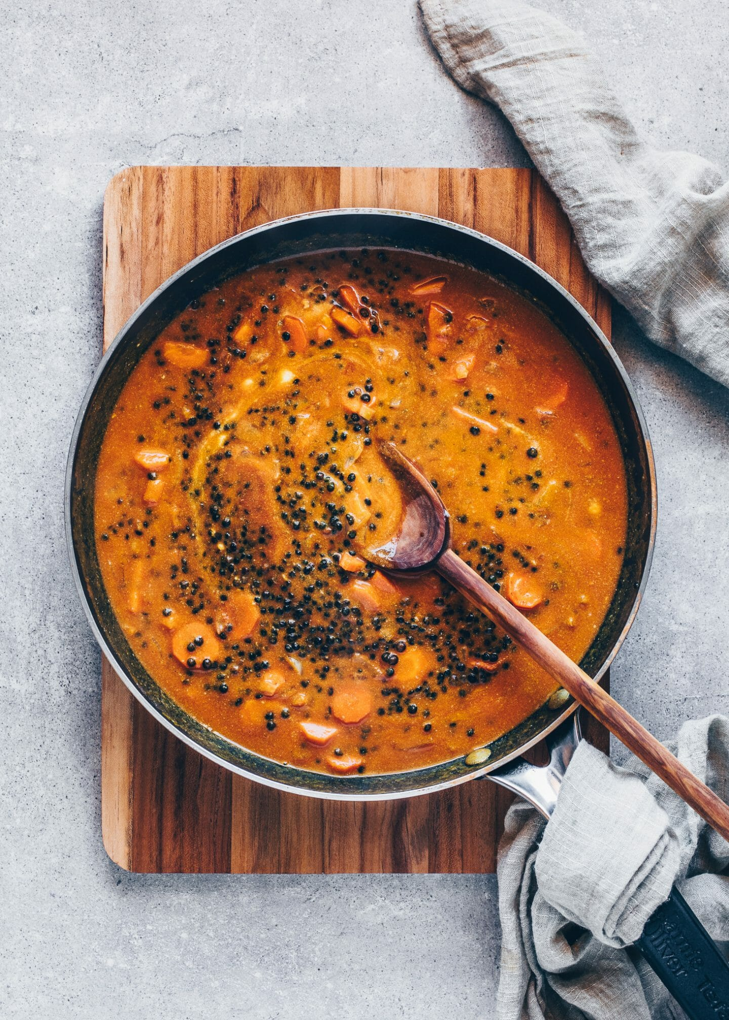 Roasted onion, garlic, ginger, carrots, black lentils, strained tomatoes, vegetable broth, and coconut milk in a skillet