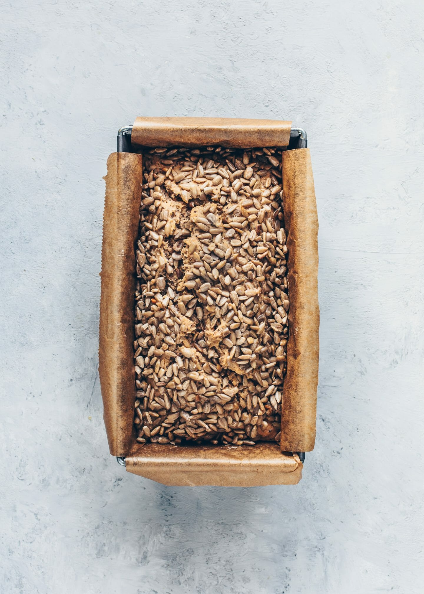 No knead paleo buckwheat chia bread with sunflower seeds in a loaf pan