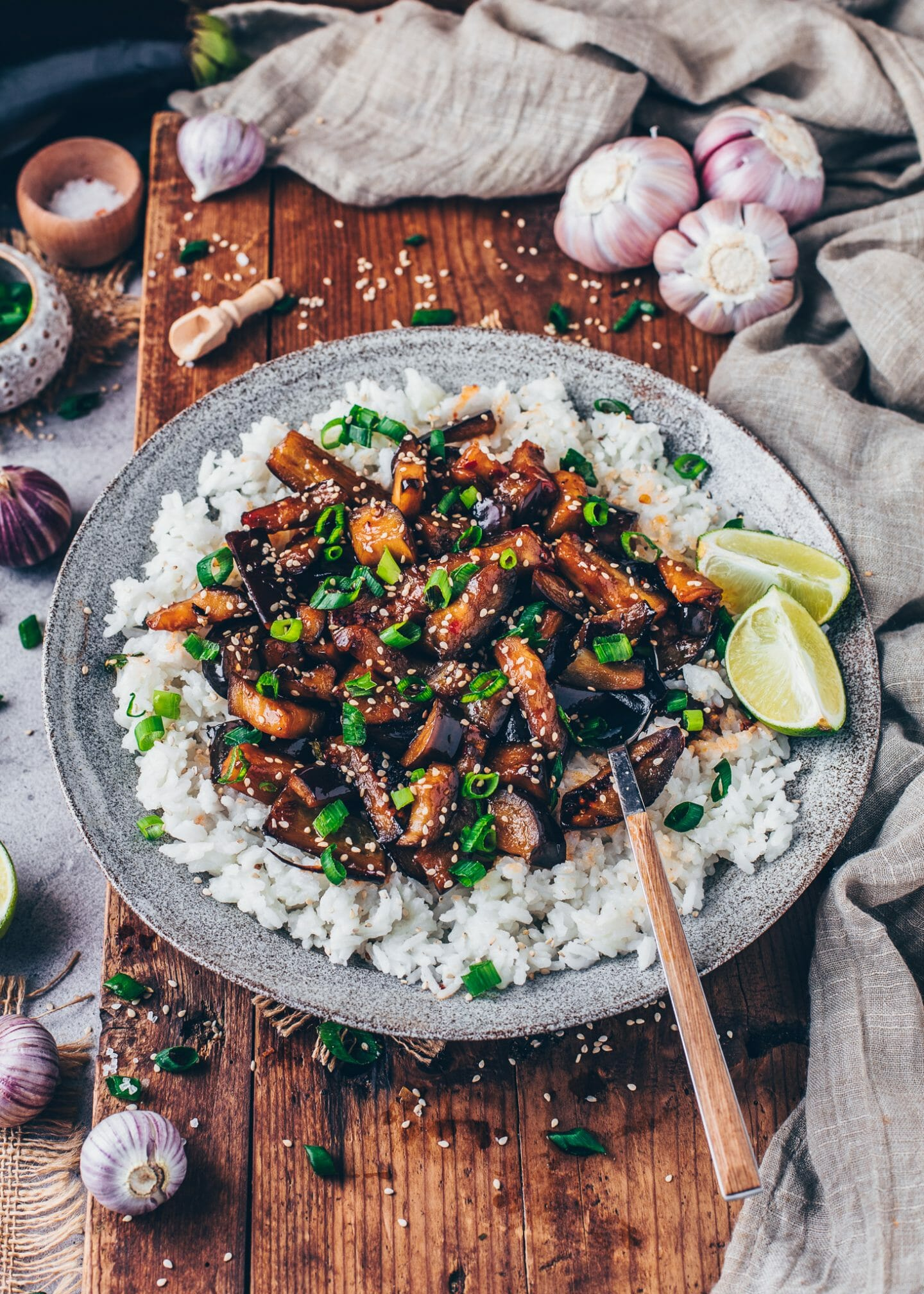 Chinese Eggplants in Chili Garlic Sauce with rice, scallions, sesame and limes