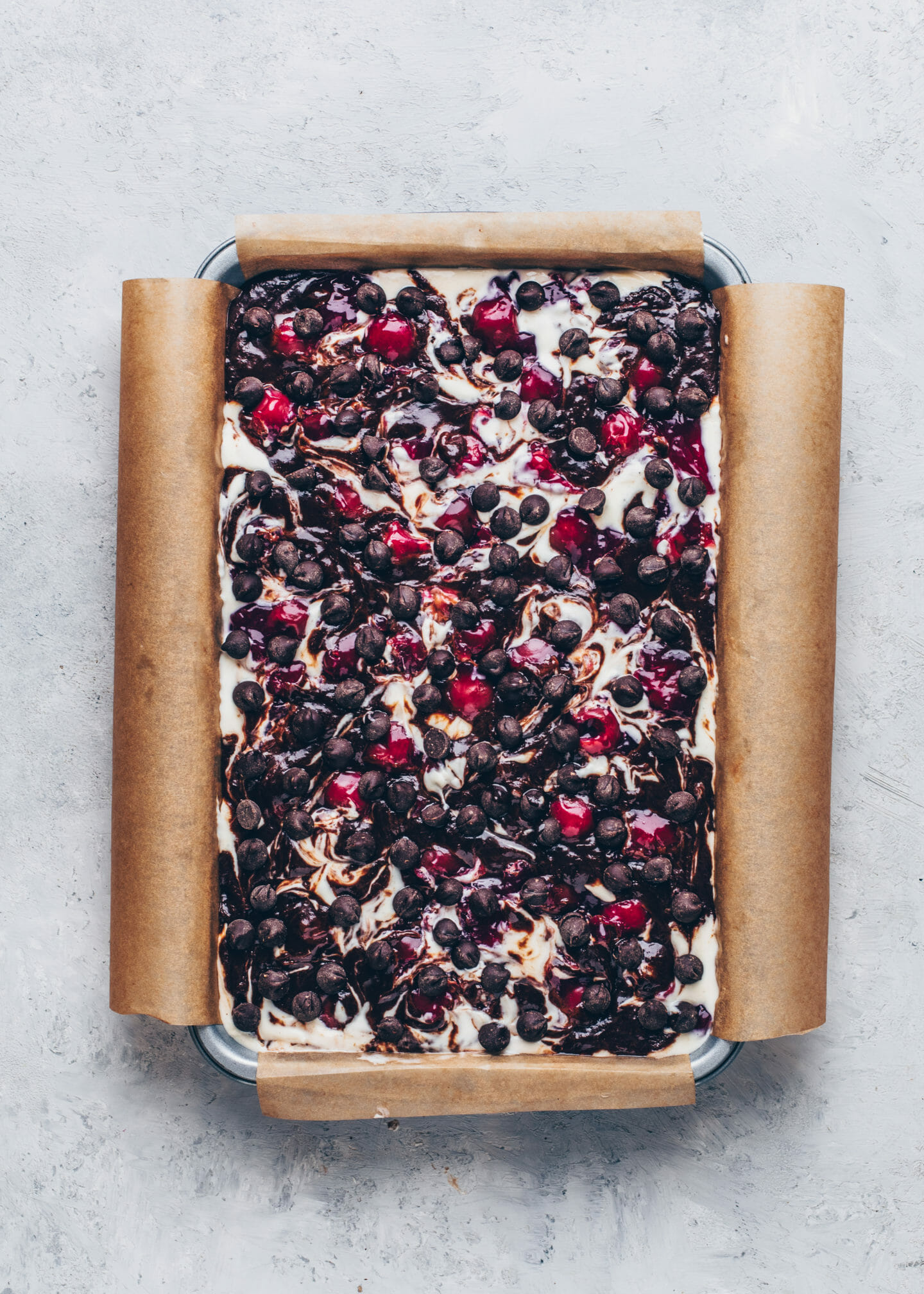 Cherry Cheesecake Swirl Brownies with vegan chocolate chips in a baking pan