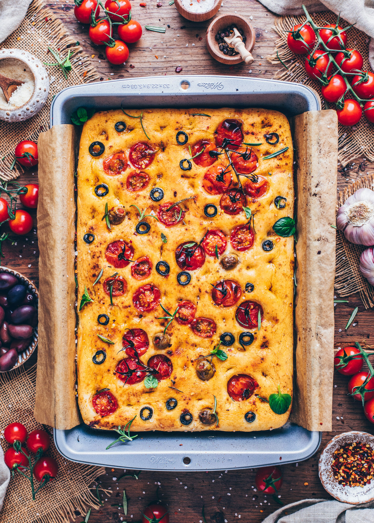 Vegan Focaccia Bread with cherry tomatoes, olives, rosemary, and sea salt