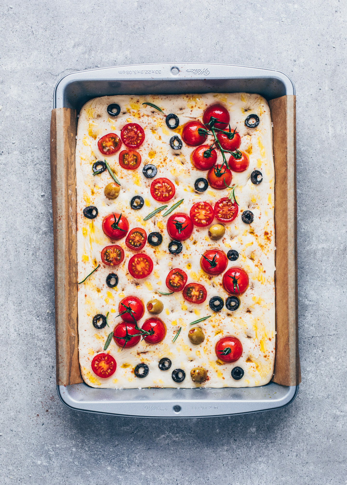 focaccia bread with tomatoes, olives, rosemary, olive oil, and sea salt