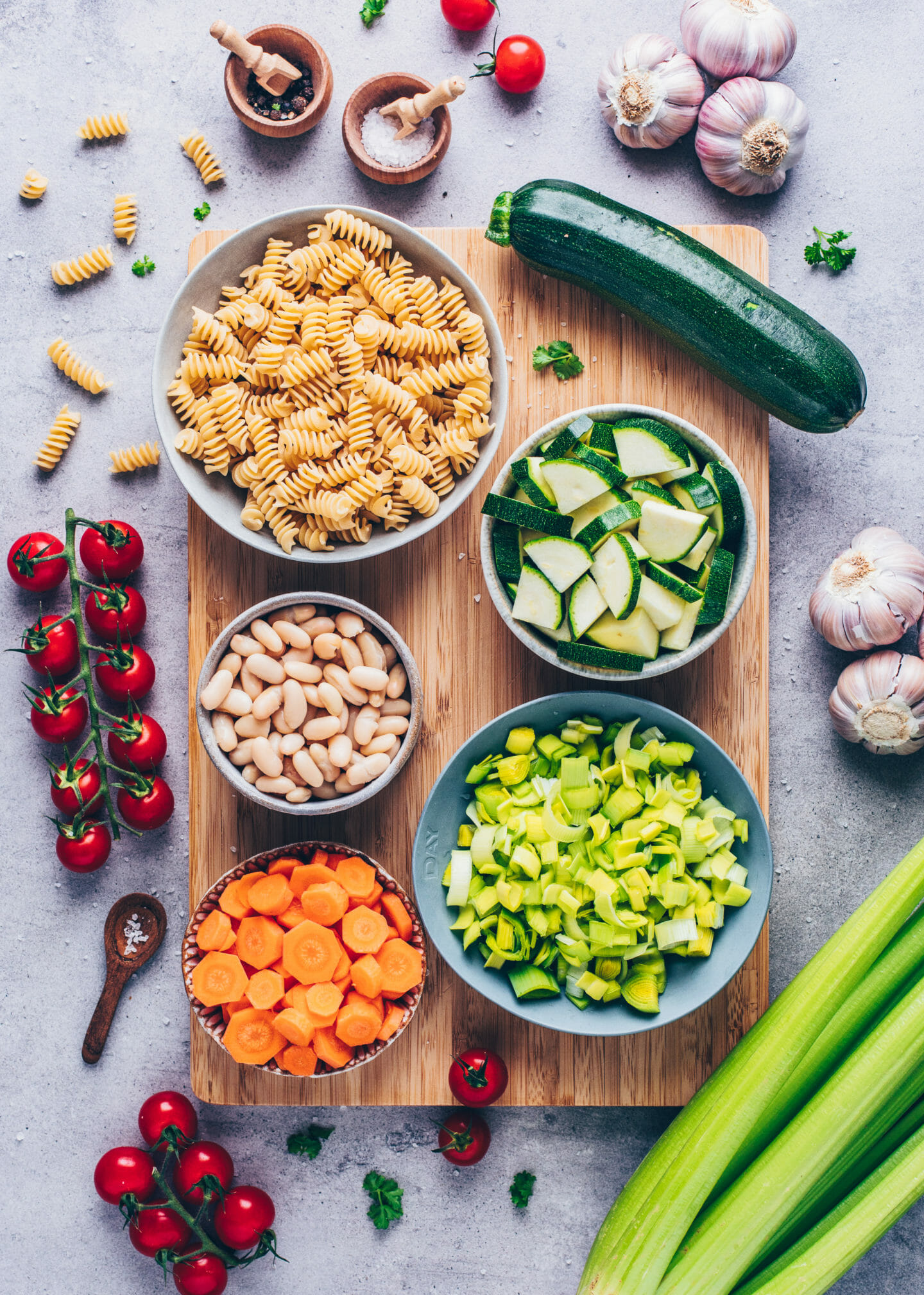 Ingredients for minestrone soup ( zucchini, carrots, leek, tomatoes, white beans and gluten-free fusilli pasta)