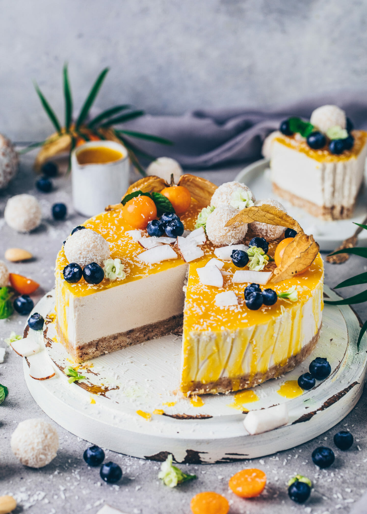 No-Bake Coconut Mango Cheesecake with vegan Raffaelo Pralines, Blueberries and Gooseberries