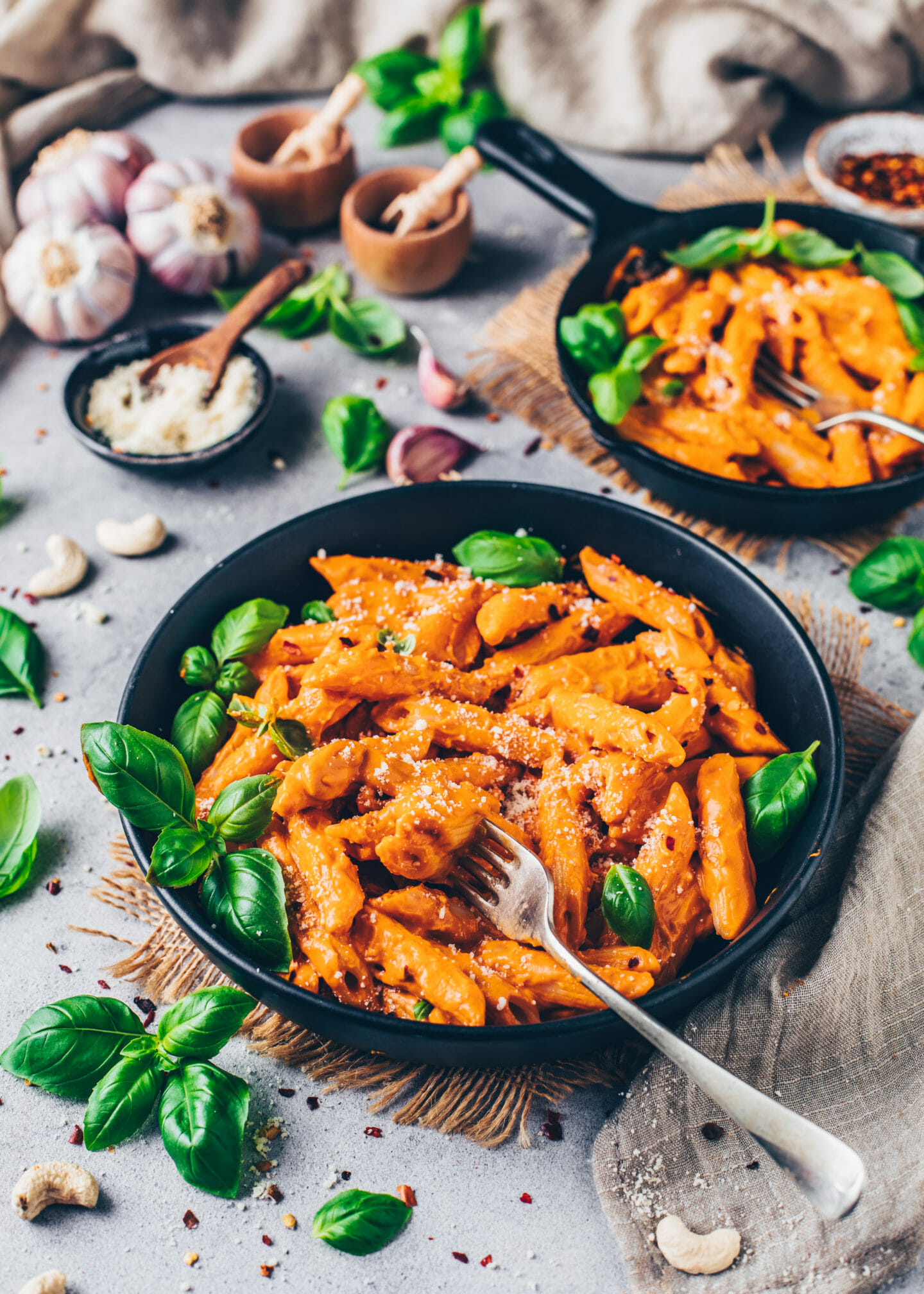 Sun-dried Tomato Cashew Penne Pasta alla Vodka with vegan parmesan cheese and basil