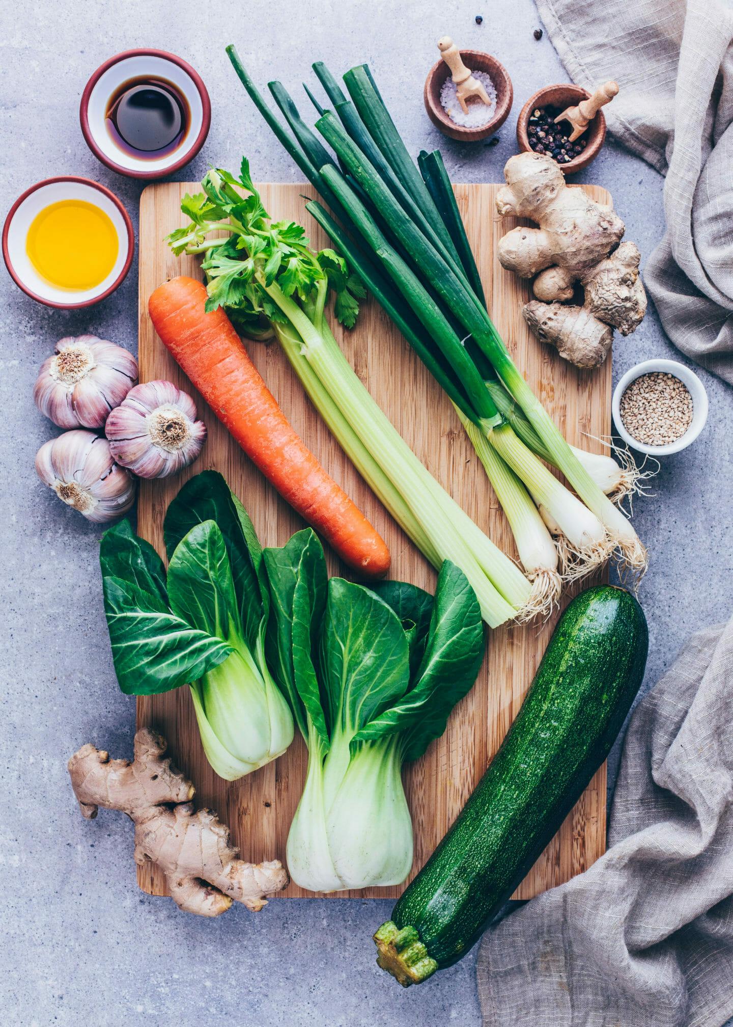 Zutaten für Asiatische Gemüsesuppe mit Knoblauch, Ingwer, Karotten, Lauchzwiebeln , Bok Choy, Zucchini, Sesam und Sojasauce