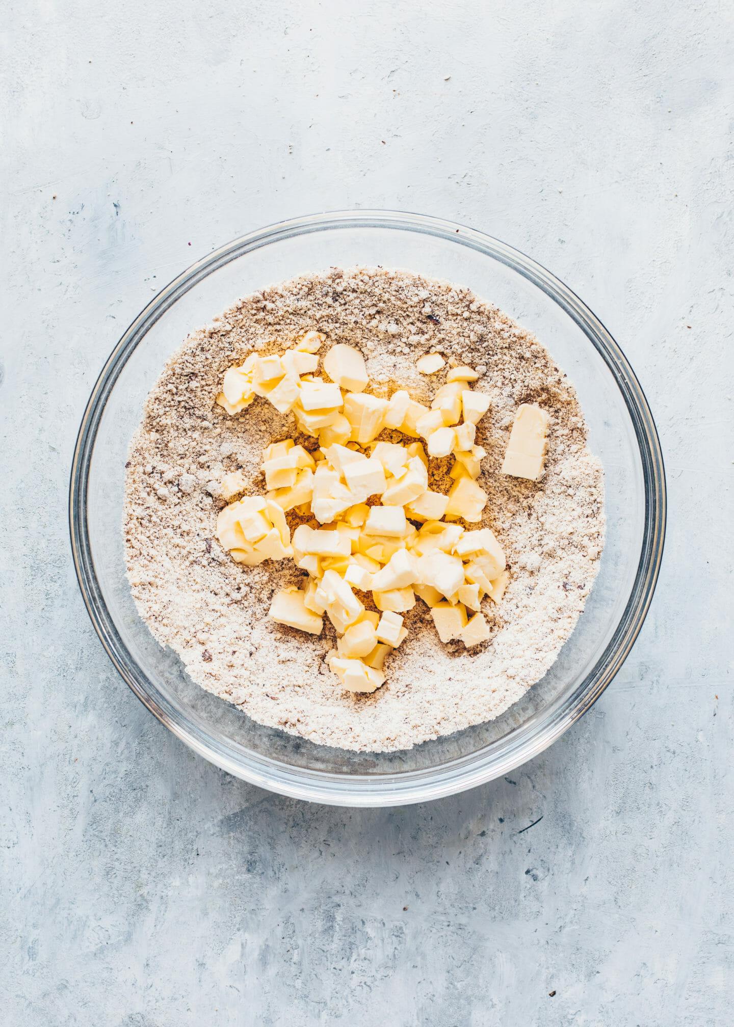 Mehl, gemahlene Haselnüsse, Kokosnusszucker, eine Prise Salz und Butter-Würfel in einer Schüssel für Haselnuss-Mürbeteig