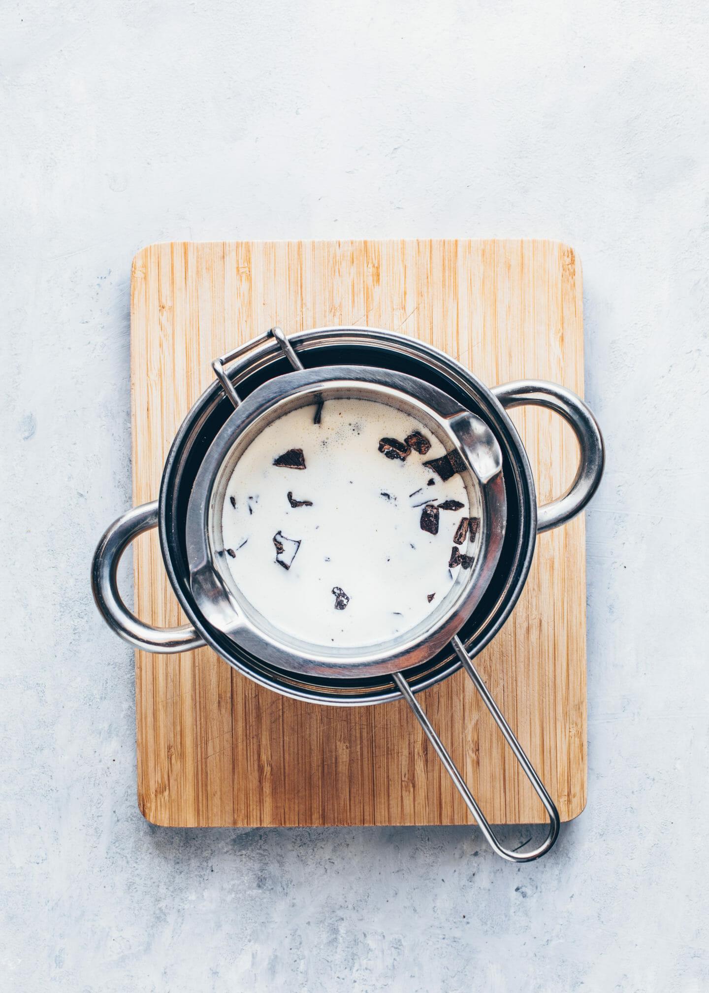 Schokolade und Kokosmilch über einem Wasserbad schmelzen für Haselnuss-Schoko-Aufstrich