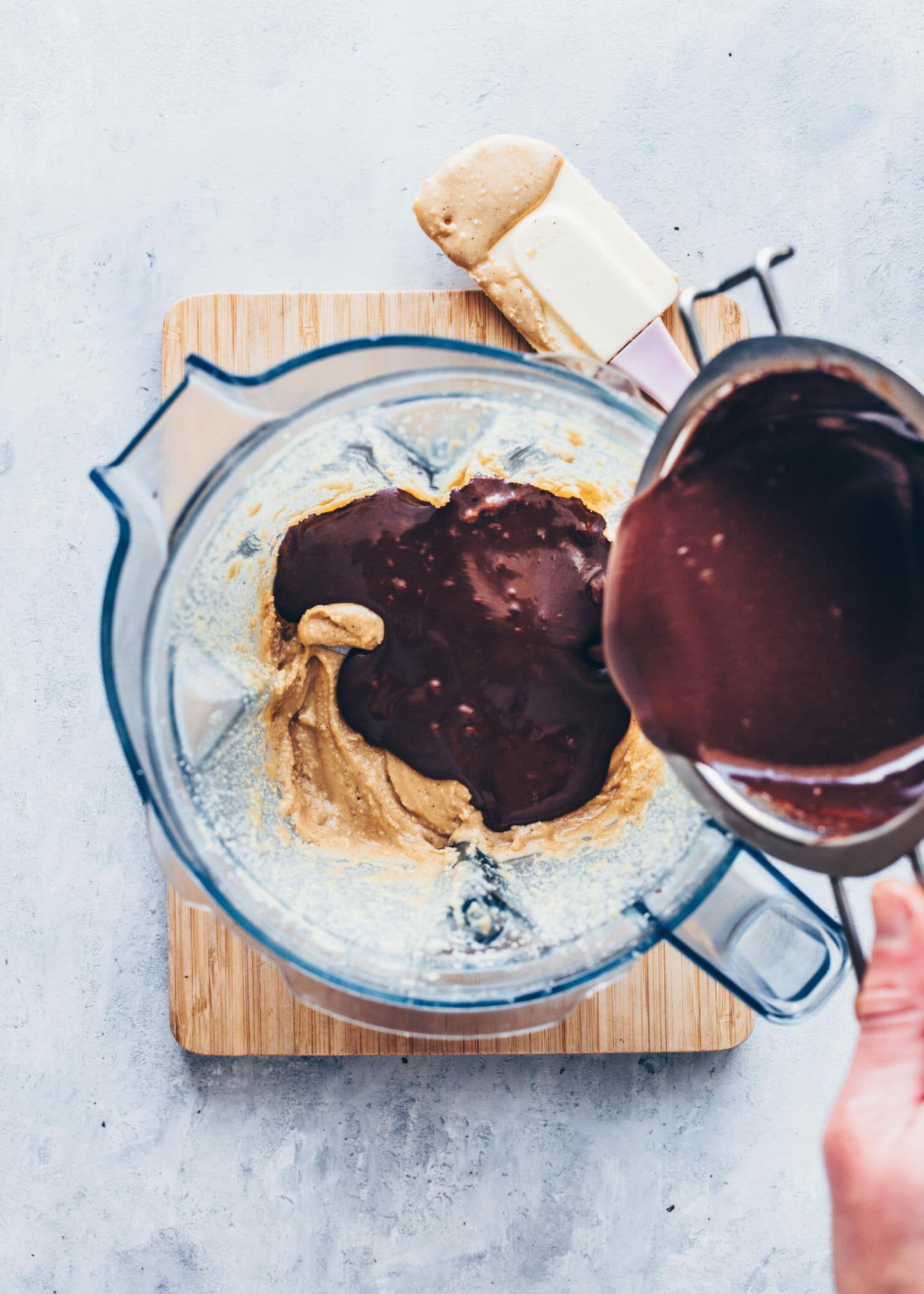 geschmolzene Schokolade in einen Mixer gießen mit Haselnussmus, Kokosmilch, Ahornsirup und Salz in einem Mixer für selbstgemachtes Nutella (Schoko-Nuss-Creme)