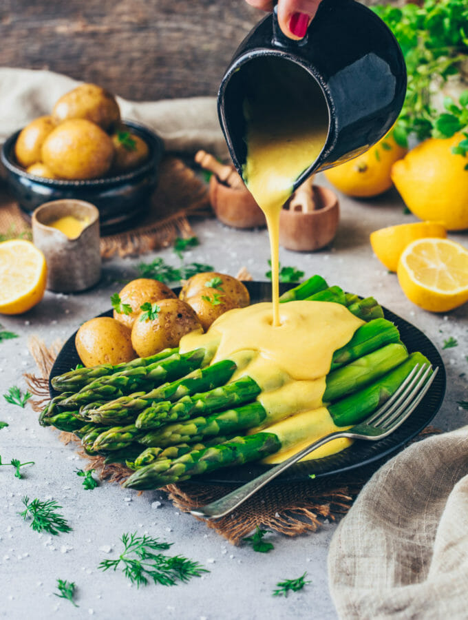 asparagus and boiled potatoes with sauce hollandaise, lemons and herbs (food photography, food styling)