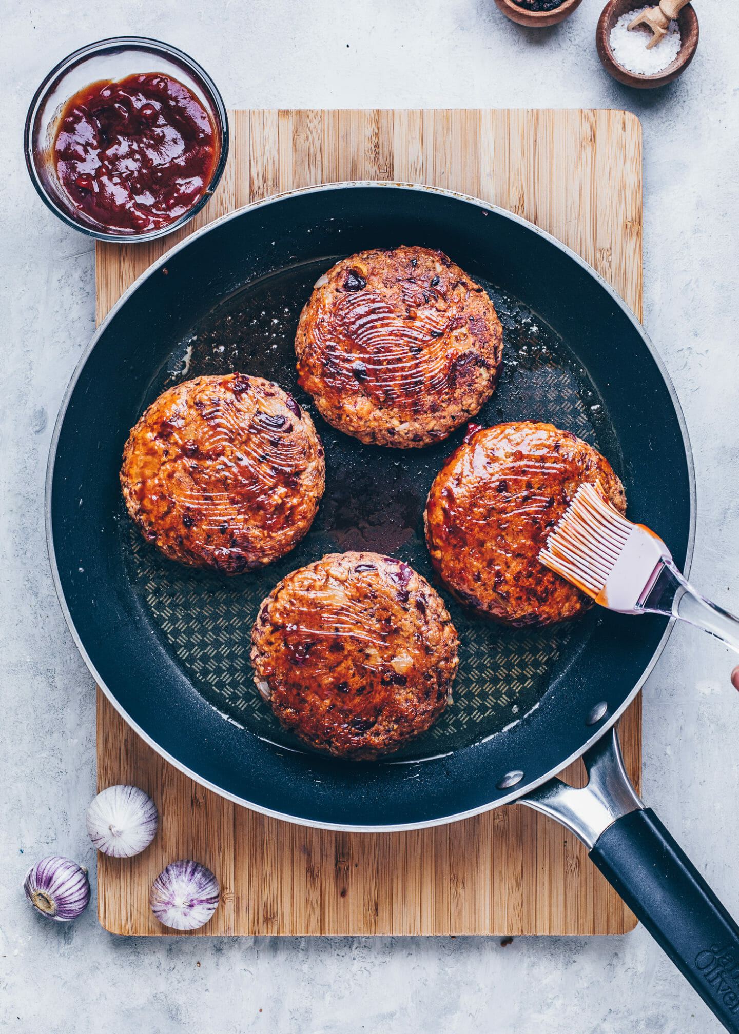 vegan burger patties in a pan with barbecue sauce